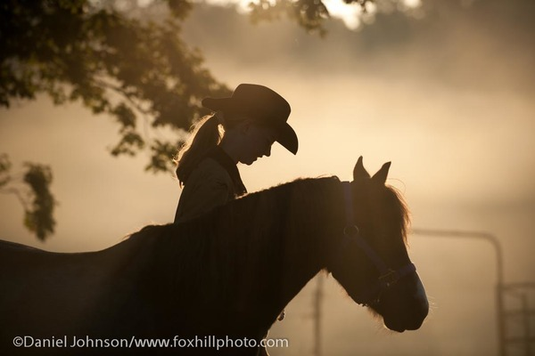 Girl with pony on a foggy morning
