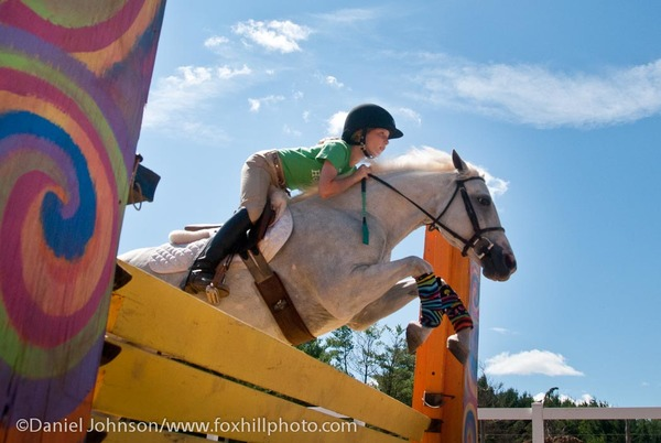 Flying over the fences, pony, child and blue skies