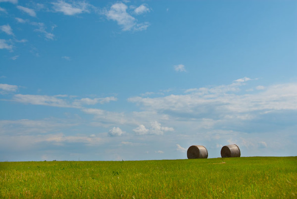 The open sky above farm fields with round bales of hay.
